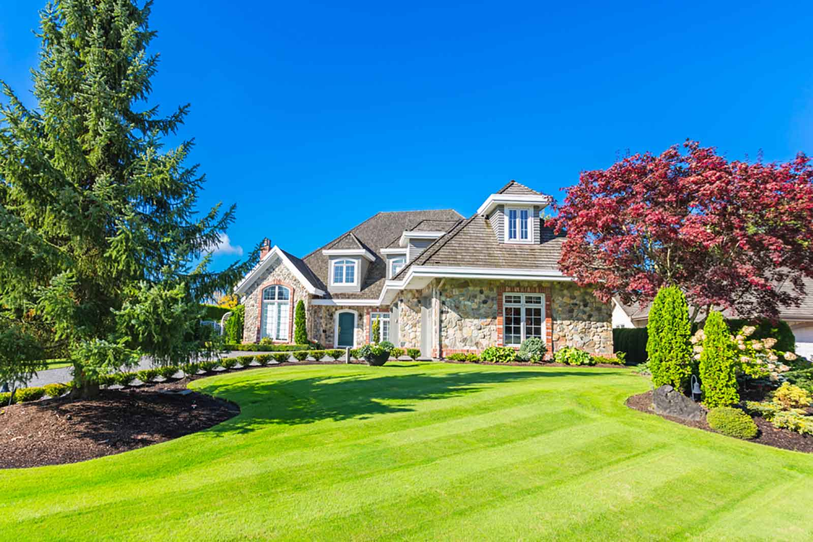 large house with a beautiful lawn and landscaping