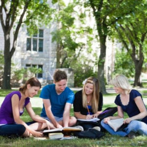 college students studying on the lawn on campus