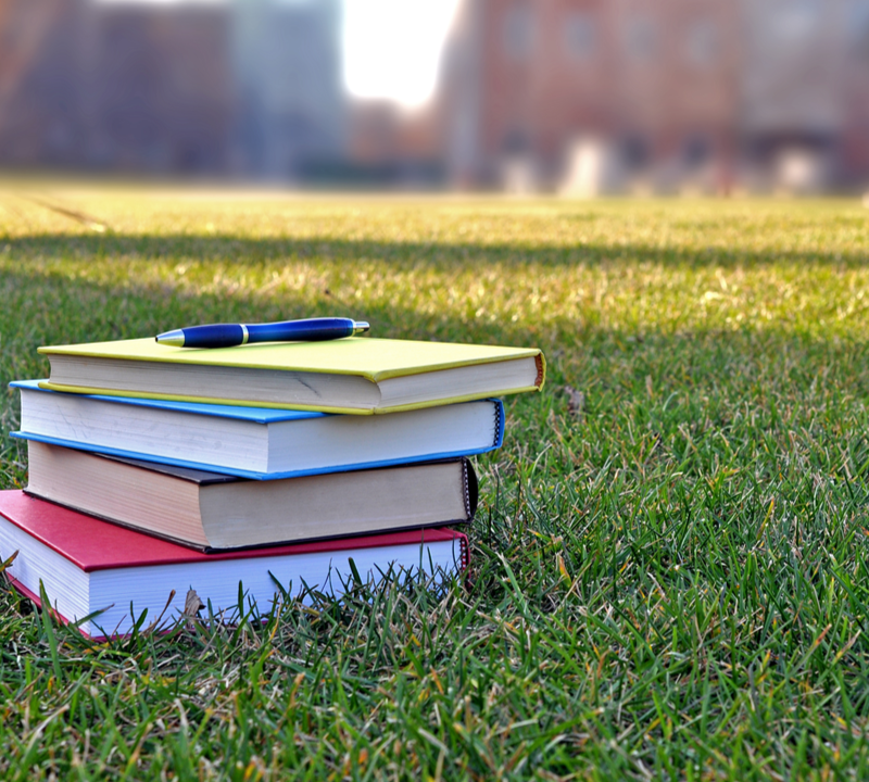 books on the lawn of a college campus